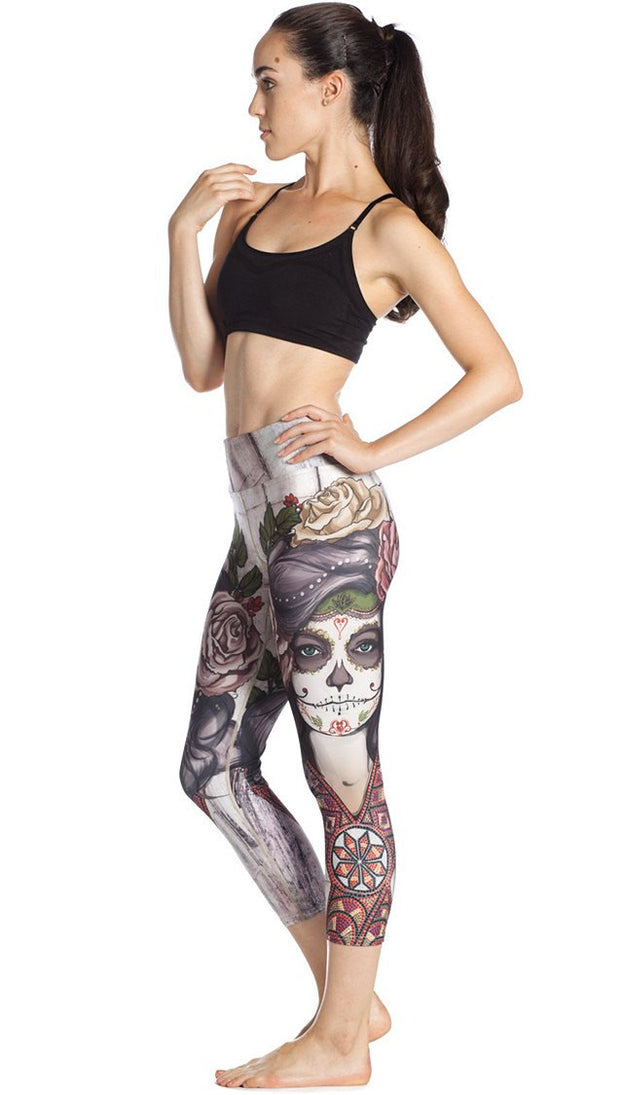 left side view of model wearing sugar skull themed printed capri leggings