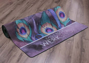 Peacock Yoga Mat rolled on the floor with peacock feathers and our logo showing on the bottom edge