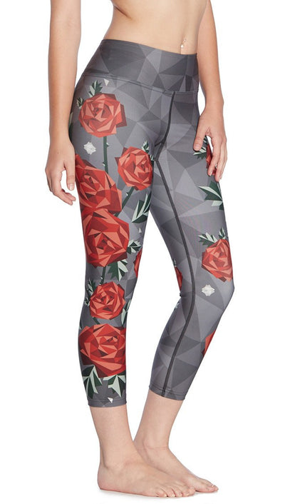 close up right side view of model wearing geometric roses themed printed capri leggings