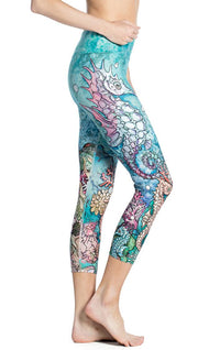 close up right side view of model wearing seahorse and coral reef themed printed capri leggings