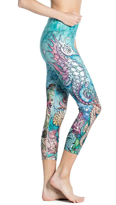close up side view of seahorse and coral reef themed printed capri leggings