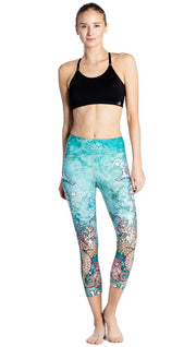 close up front view of model wearing seahorse and coral reef themed printed capri leggings
