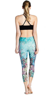 back view of model wearing seahorse and coral reef themed printed capri leggings