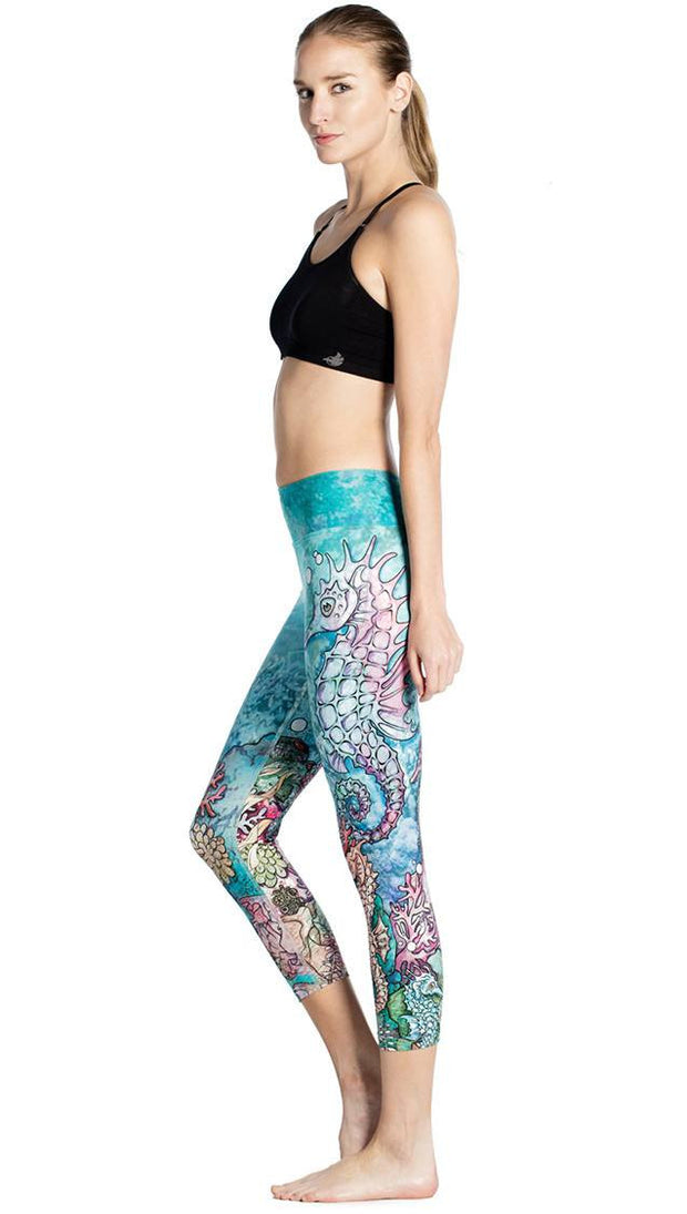 left side view of model wearing seahorse and coral reef themed printed capri leggings