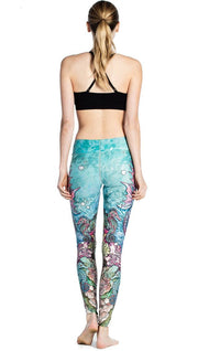 back view of model wearing colorful seahorse themed printed full length leggings