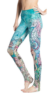 close up left side view of model wearing colorful seahorse themed printed full length leggings