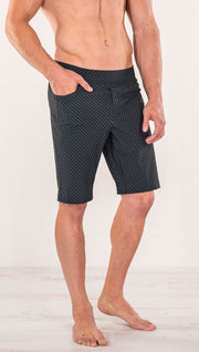 Close up diagonally right side view of model wearing men's black printed performance shorts with slim fit and carbon fiber inspired art.