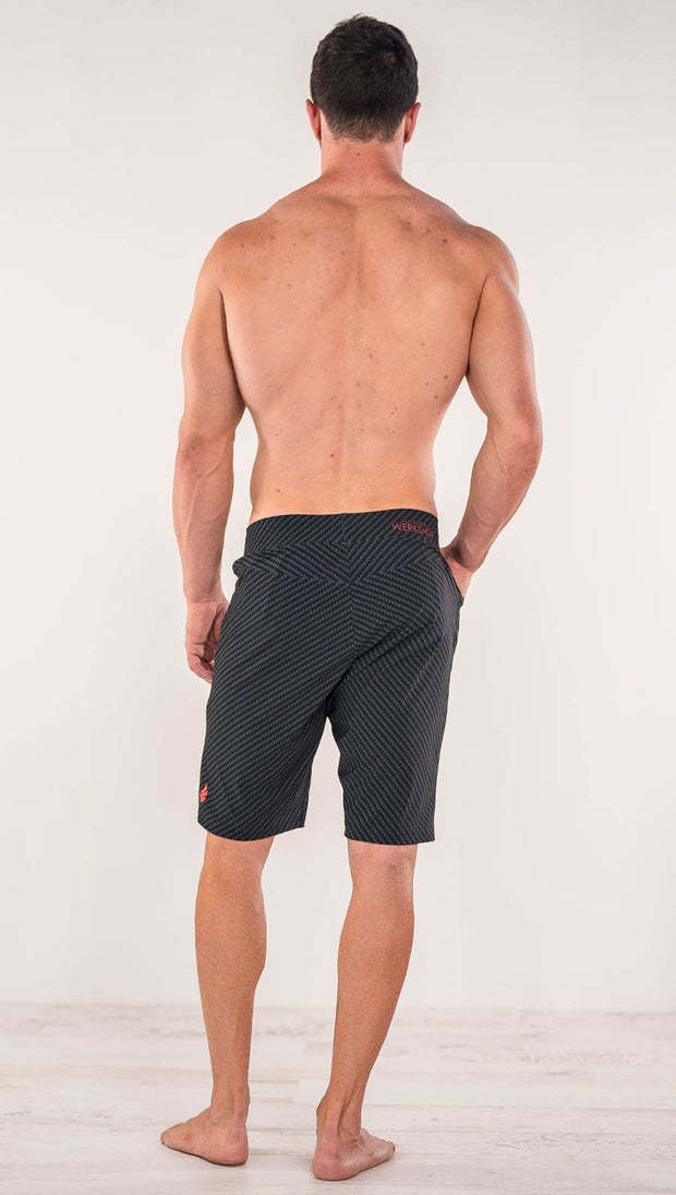 Back view of model wearing men's black printed performance shorts with slim fit and carbon fiber inspired art.