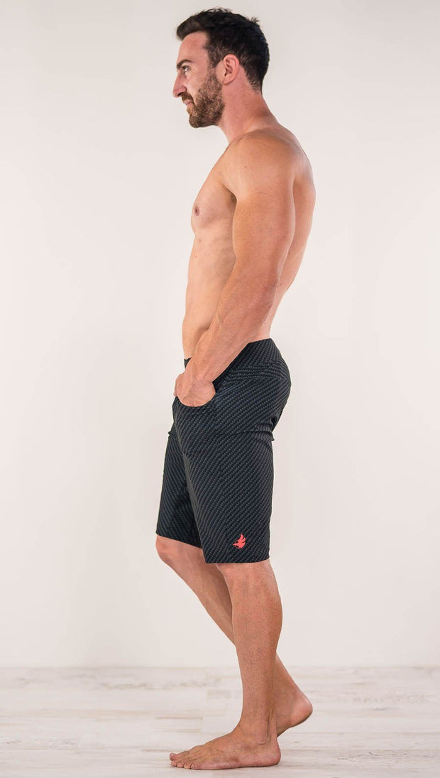 Right side view of model wearing men's black printed performance shorts with slim fit and carbon fiber inspired art.