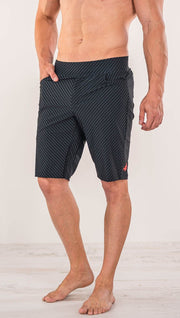 Close up front view of model wearing men's black printed performance shorts with slim fit and carbon fiber inspired art.