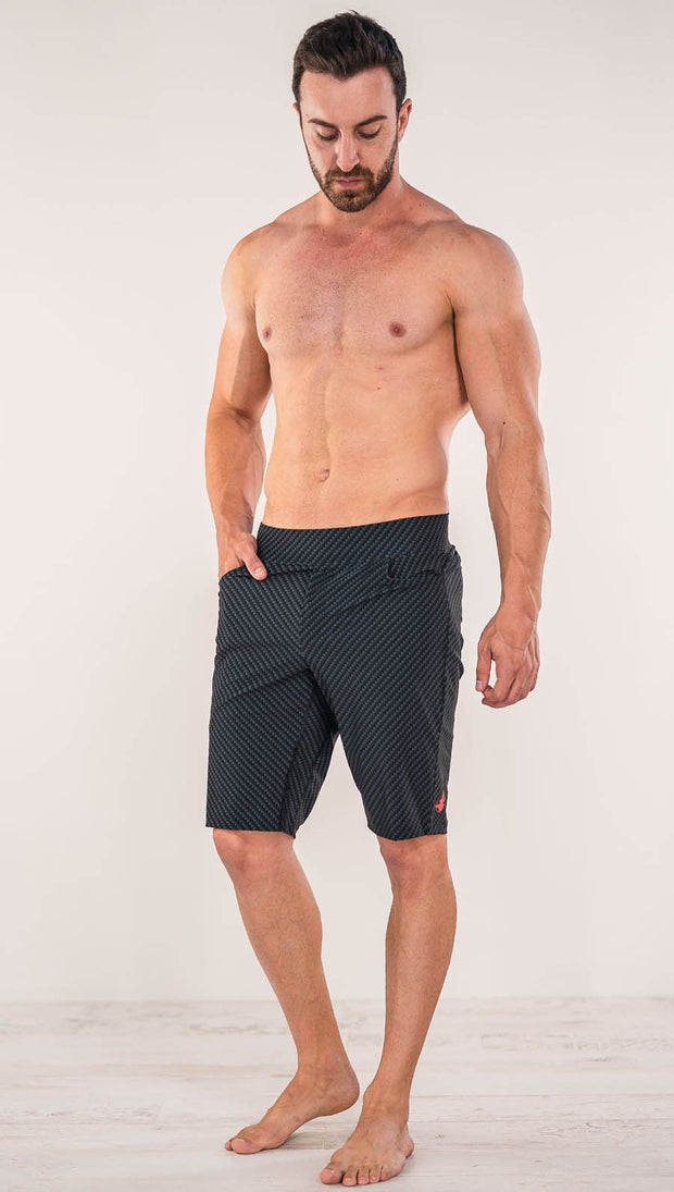 Front view of model wearing men's black printed performance shorts with slim fit and carbon fiber inspired art.