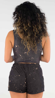 Back view of model wearing a reversible crop top in a dark charcoal color with beige splatter spots throughout on this side