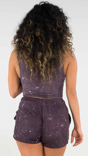 Back view of model wearing a reversible crop top in purple with light gray splatter spots throughout on this side