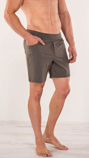 Close up right side view of model wearing men's taupe performance shorts with slim fit
