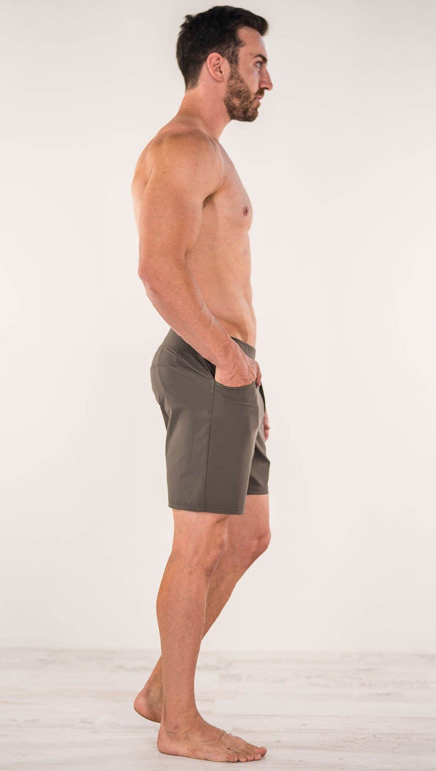 Right side view of model wearing men's taupe performance shorts with slim fit