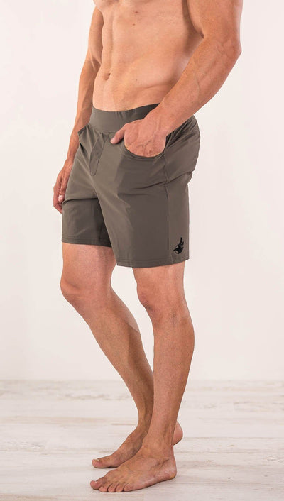 Close up left side view of model wearing men's taupe performance shorts with slim fit