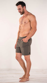 Left side view of model wearing men's taupe performance shorts with slim fit