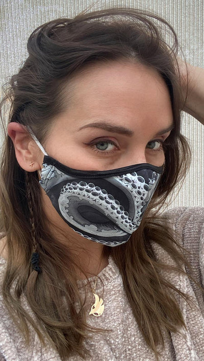 Right side view of model wearing a black mask with large white and grey tentacles