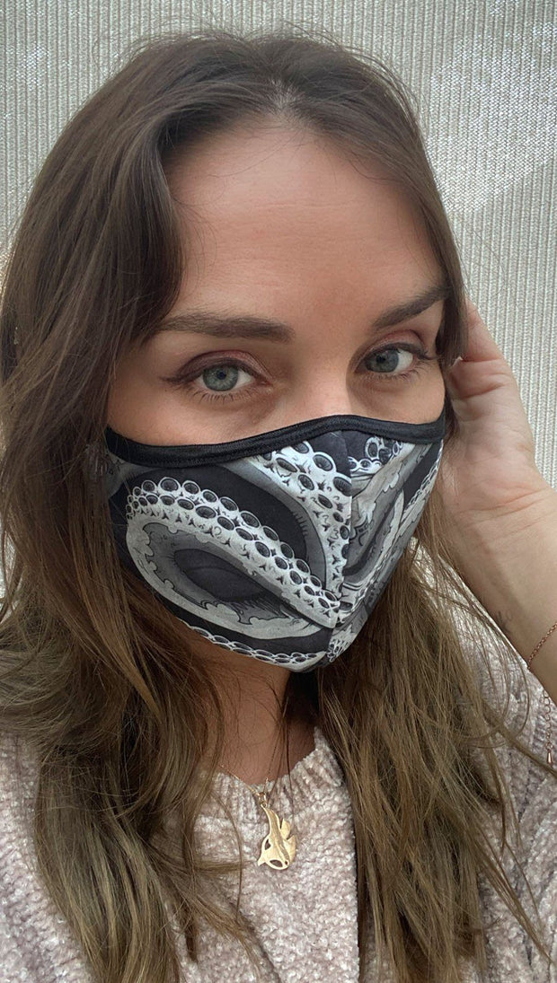Front view of model wearing a black mask with large white and grey tentacles