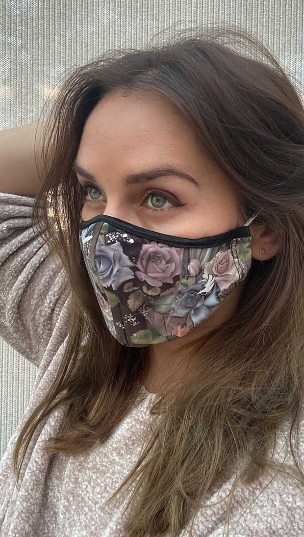 Left side view of model wearing a mask with pink and blue roses