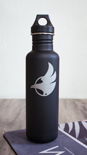 Black water bottle with Eagle Rock Werkshop logo resting on a purple yoga mat with Eagle Rock Werkshop logo.