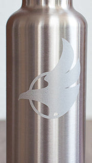 Closeup of silver water bottle with Eagle Rock Werkshop logo resting on a purple yoga mat with Eagle Rock Werkshop logo.