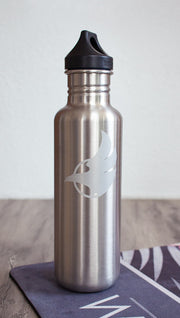 Silver water bottle with Eagle Rock Werkshop logo resting on a purple yoga mat with Eagle Rock Werkshop logo.