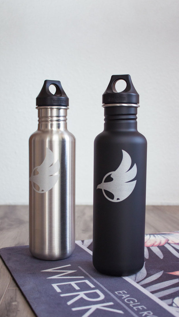 Black water bottle with Eagle Rock Werkshop logo next to silver water bottle with Eagle Rock Werkshop logo resting on a purple yoga mat with Eagle Rock Werkshop logo.