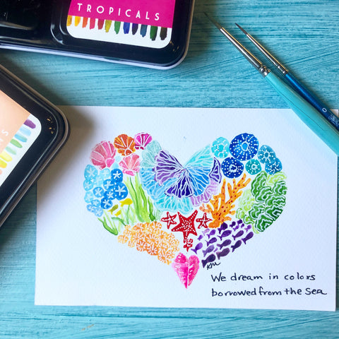 painted postcard of a heart with sea life in it along with paintbrush and watercolor paints