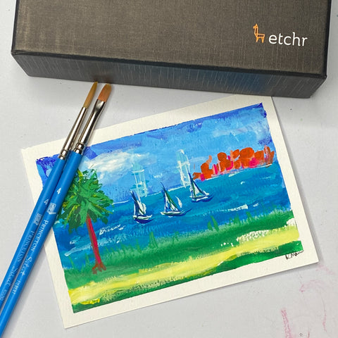 watercolor postcards, paintbrush and a postcard with sailboats on it