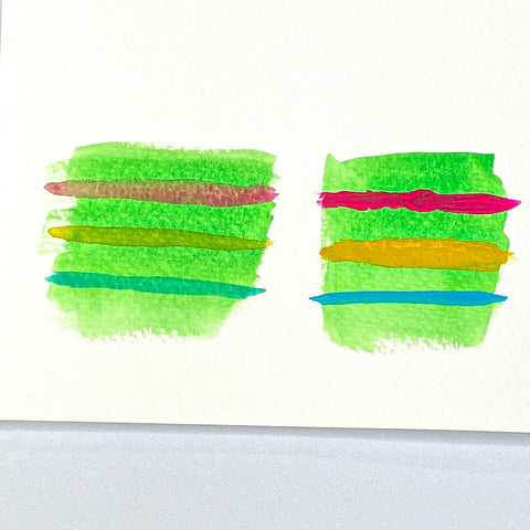 Two painted squares of Green watercolor with pink, yellow and teal stripes across each square.