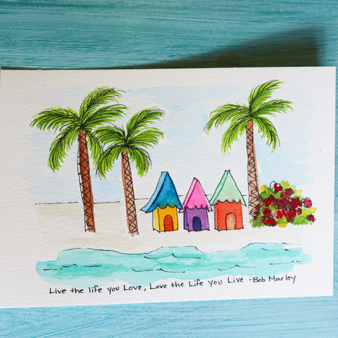 """Postcard with small illustration beach houses and palm trees with Bob Marley quote, """"live the life you love, love the life you live"""""""