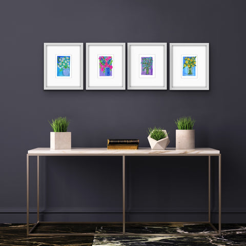 4 gouache floral paintings matted and framed above a metal end table with small plants