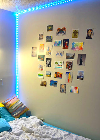 college apartment bedroom with postcards displayed on the wall as decoration