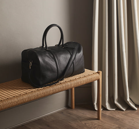Black Weekender Bag on wicker bench in room next to curtain