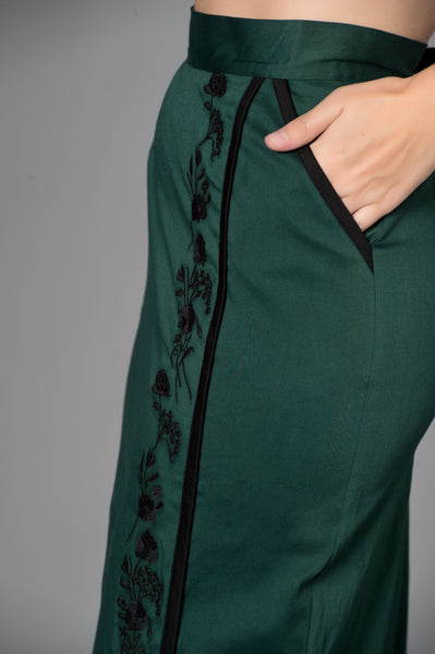 Timeless London forest green satin Quisha pencil skirt with black floral embroidered detail. Made sustainably.