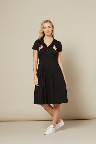 Timeless London black Crystal 40's inspired shirt dress features embroidered robin bird below open V-neck collar. Fitted body with button down front and flared skirt. Made sustainably.