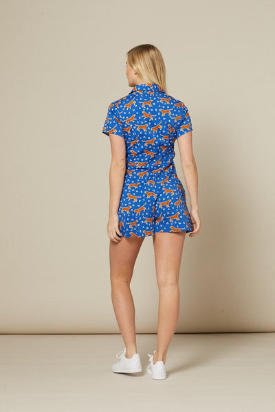 Timeless London cobalt blue Tessa ditsy playsuit features orange and white leopard print pattern. Slim fit with open V-neck collar. Sustainably made.