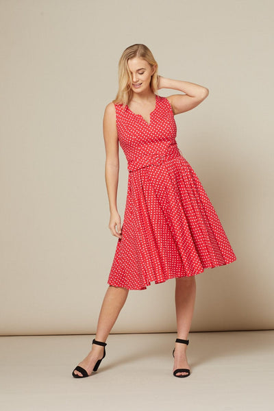 Timeless London red Timmy skater dress, with white polka dot print and matching belt. Featured a fitted waist and flared below knee length swing skirt, a round neck with unique v-cut out.