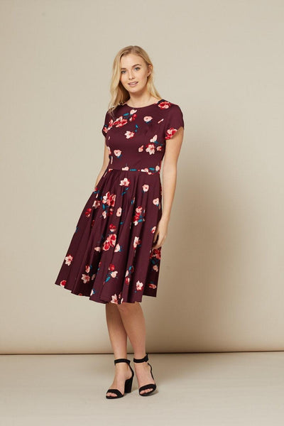 Timeless London Abigail Burgundy flared skater dress with red white green floral print. Fitted with high neck and short sleeves, and features a lightly gathered swing skirt. Made sustainably.