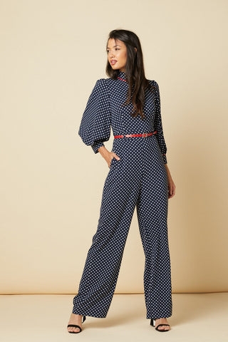 Timeless London White and Blue Nelly jumpsuit, featuring polka dot print and red belt. With high neck and shoulders, puff sleeves and long straight legs. Made sustainably.