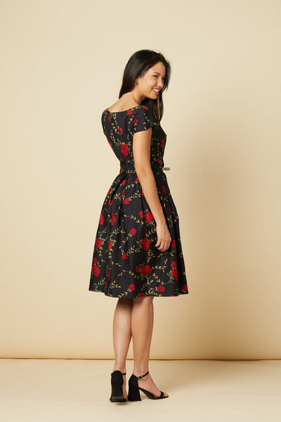 Timeless London black Stacey fifties swing dress, features red floral print with matching adjustable waist tie. With fitted waist, scoop neck and flared swing skirt. Made sustainably.