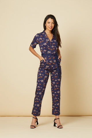 Timeless London navy Wild Horses jumpsuit featuring horse and floral print. Ankle length straight legs have pockets, with short sleeves and open collared v-neck, and adjustable navy waist tie. Made sustainably.