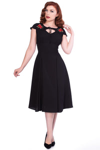 Timeless London black Juliana dress with red floral embroidered shoulder panels and ribbon embellished large key hole cut out. With a fitted waist, lightly ruched bust and flared below the knee skirt. Sustainably made.