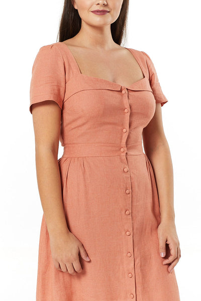Timeless London Micaela peach orange pastel lace up back dress, with low boat neck, frontal buttons, a fitted waist and flared skirt.