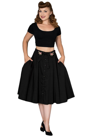Timeless London black Paulette swing skirt, features pink floral embroidered detail, black ribbon and button down front. Made sustainably.