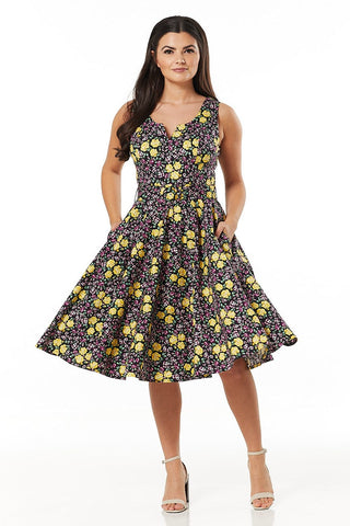 Ria black, white, purple and yellow floral swing dress, with fitted waist, matching belt, 50's flared skirt with pockets and boat neck featuring V-neck cut out. Made sustainably.