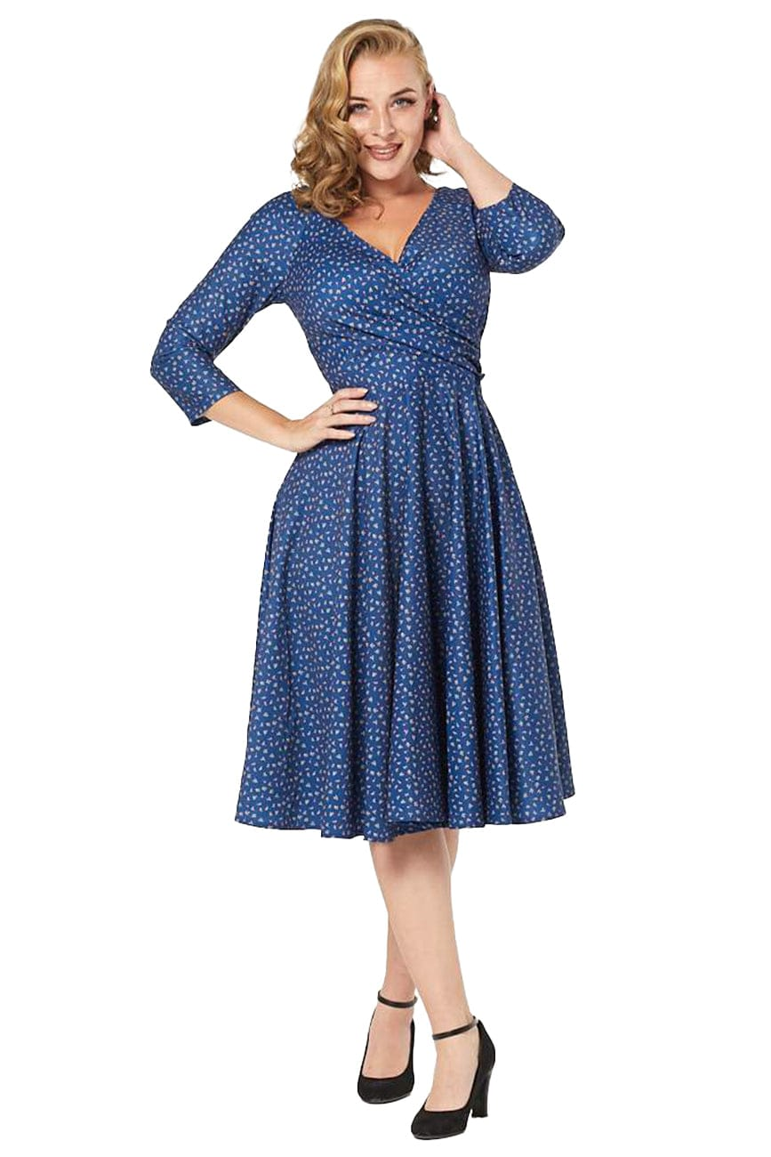 Timeless London blue Lottie fifties style swing dress, featuring floral print and wrap over feature on bust, with flared below knee swing skirt. Made sustainably.