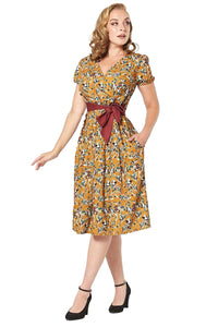 Timeless London mustard yellow Liby fifties swing dress, featuring white floral print and burgundy adjustable waist tie. With Faux wrap over detail at bust, V-neck, fitted waist and flared skirt. Made sustainably.
