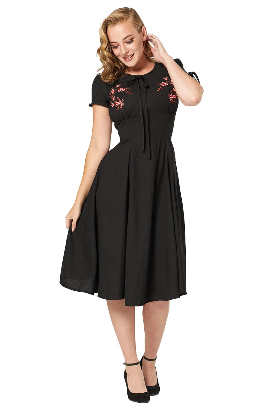 Timeless London black Palmer 40's style hand embroidered dress featuring floral pattern and ribbon detail on round neckline and short sleeves. With fitted waist, lightly ruched bust and flared swing skirt. Made sustainably.